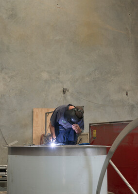 Staff member welding stainless steel in our factory